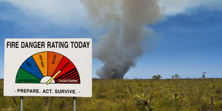 Bush fire danger. Fire Danger Rating Display Board set to extreme in front of bushfire. Image taken in Queensland, Australia Royalty Free Stock Photo