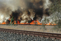 Bush fire beside railway line Royalty Free Stock Photos