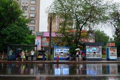 Bushalte met mensen die op een warme regenachtige de zomerdag wachten Royalty-vrije Stock Fotografie
