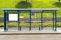 Bushaltestelle mit einer Anschlagtafel stockbilder