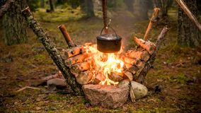 Bushcraft setting with a camping pot hanging over a burning fire. A camping kettle is hanging over a burning fire with a reflector in the background made from stock images