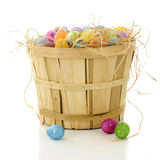 Bushel Basket Full of Easter. A bushel basket filled with straw and colorful Easter eggs. On a white background stock photography