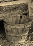 Bushel Basket, a form of measurment. Bushel Basket with a log cabin background shown in Sepia-tone stock photo