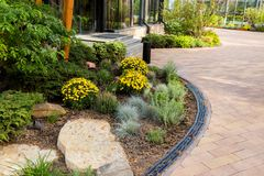Bushes and flowers in landscape design. Of paths in the yard stock photos