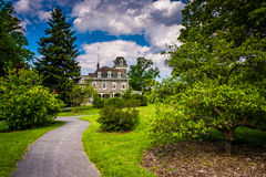 Bushes and trees along a path and the Cylburn Mansion at Cylburn Royalty Free Stock Images