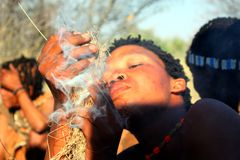 Bushman. A indigenous bushman in the Kalahari desert making fire with gras Stock Photos