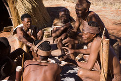 Bushman family. Sitting around a fire in namibia Stock Photos