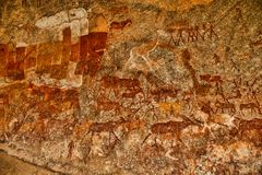 Bushmen rock painting of human figures and antelopes, giraffe of the Matopos National Park, Zimbabwe. The Bushmen rock painting of human figures and antelopes Stock Images