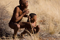 Bushmen. San family, demostration how to start a hunting in the early morning Royalty Free Stock Images
