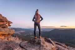 Bushwalker op top van berg met valleimeningen stock foto's