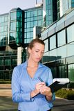 Busiensswoman. Young busiensswoman examining papers in front of the building royalty free stock photography