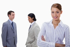 Busiensswoman with arms folded and talking colleagues behind her Royalty Free Stock Photos