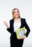 Busiensswoman holding cup of coffee and big clock Royalty Free Stock Image