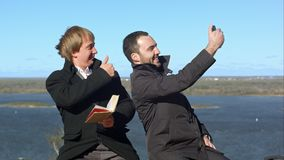 Busineeman, das Daumen-oben gibt und draußen selfies auf der Bank macht Stockfotografie