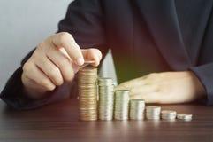 Busineeman ha messo i soldi sul porcellino salvadanaio sullo scrittorio Immagine Stock Libera da Diritti