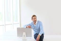 Busineesman sitting on desk leaning on monitor Royalty Free Stock Photo