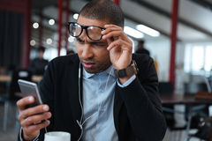 Busineessman touching his glasses and reading message on the smartphone Royalty Free Stock Image