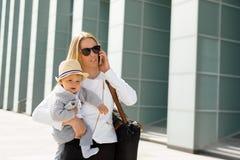busines的Susccessful母亲走与婴孩的在她的手上 免版税库存图片