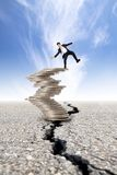 Busines and Economic crisis concept. Cracked road and unstable businessman on the money tower Stock Image