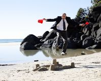 Busines frustration. A well dressed businessman jumping in the air above a sand castle, signifying a major business breakdown stock images