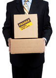 Busines man holding box with copy space. Man in a business suit holding moving boxes with a fragile sticker on it on a white background Stock Image