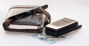 Busines scene. A Filofax cell phone and some money lying together Royalty Free Stock Photography