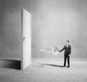 Businesman closed door. Young man holding big key with closed door Royalty Free Stock Photography