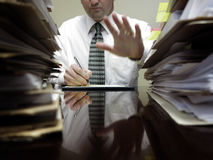 Businesman at Desk with Piles of Files and Papers. Businessman at desk with piles of files, papers and a notebook pen Royalty Free Stock Photo