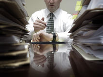 Businesman at Desk with Piles of Files and Papers Royalty Free Stock Photo