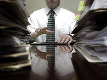 Businesman at Desk with Piles of Files and Papers Stock Photography