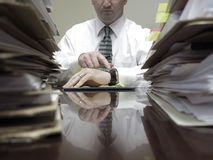 Businesman at Desk with Piles of Files and Papers. Businessman at desk with piles of files, papers and a notebook pen Stock Image
