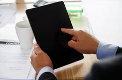 Businesman finger pointing to blank tablet. Businesman finger pointing to blank digital tablet pc on wooden working table with contract paper. Business concept Stock Images