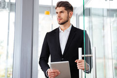 Businesman holding tablet and entering the door in office. Serious young businesman holding tablet and entering the door in office royalty free stock images
