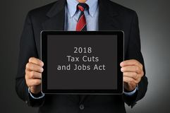 Businesman Holding Tablet with 2018 Tax Cuts and Jobs Act. Closeup of a businessman holding Tablet Computer with 2018 Tax Cuts and Jobs Act on the screen royalty free stock photo