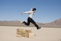 Businesman jumping over boxes Royalty Free Stock Images