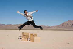 Businesman jumping over boxes Royalty Free Stock Photo