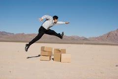 Businesman jumping over boxes Stock Photos