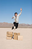 Businesman jumping over boxes Stock Photos