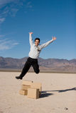 Businesman jumping over boxes Stock Photography