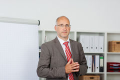 Businesman looking seriously. Businesman standing by flipchart and looking seriously Royalty Free Stock Images