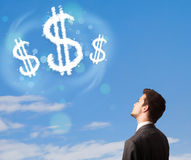 Businesman pointing at dollar sign clouds on blue sky Royalty Free Stock Photos