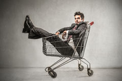 Businesman into a shopping cart Stock Images