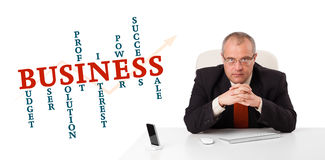 Businesman sitting at desk. With business word cloud, isolated on white Royalty Free Stock Photo