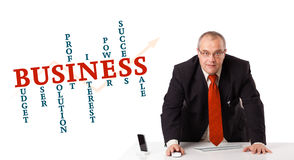 Businesman sitting at desk with business word cloud. Isolated on white Royalty Free Stock Photo