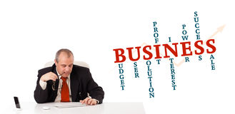 Businesman sitting at desk with business word cloud Stock Photo