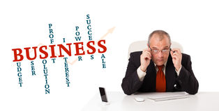 Businesman sitting at desk with business word cloud Royalty Free Stock Photography