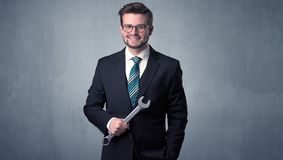 Businesman standing with tool on his hand Stock Image