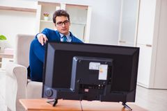 The businesman watching tv in office. Businesman watching tv in office Stock Photo