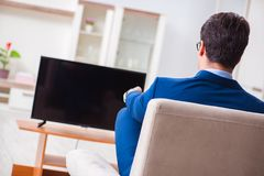 The businesman watching tv in office. Businesman watching tv in office Stock Photos