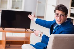 The businesman watching tv in office. Businesman watching tv in office Stock Image